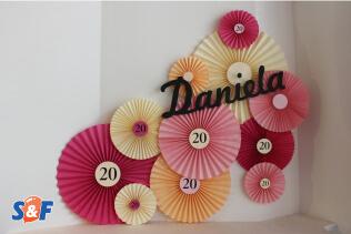 Respaldo fotográfico de rocetones y abanicos elaborados en papel, en colores rosados, fucsias y crema, con nombre Daniela en frente