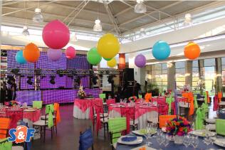 Decoración de 15 Años con globos gigantes en el techeo, menaje en colores neón y miniteca con pantallas LED